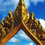 Gold temple ornament against blue skies